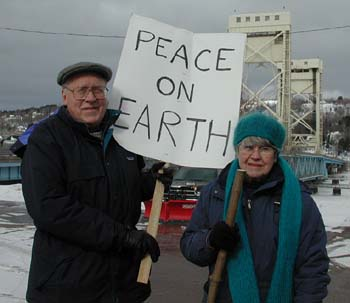 "Bob and Viola Brown, of Houghton, founding members of the Copper Country Peace Alliance, pause near the Portage Lift Bridge during a ""Walk for Peace"" in March 2002. (Photo by Michele Anderson)"