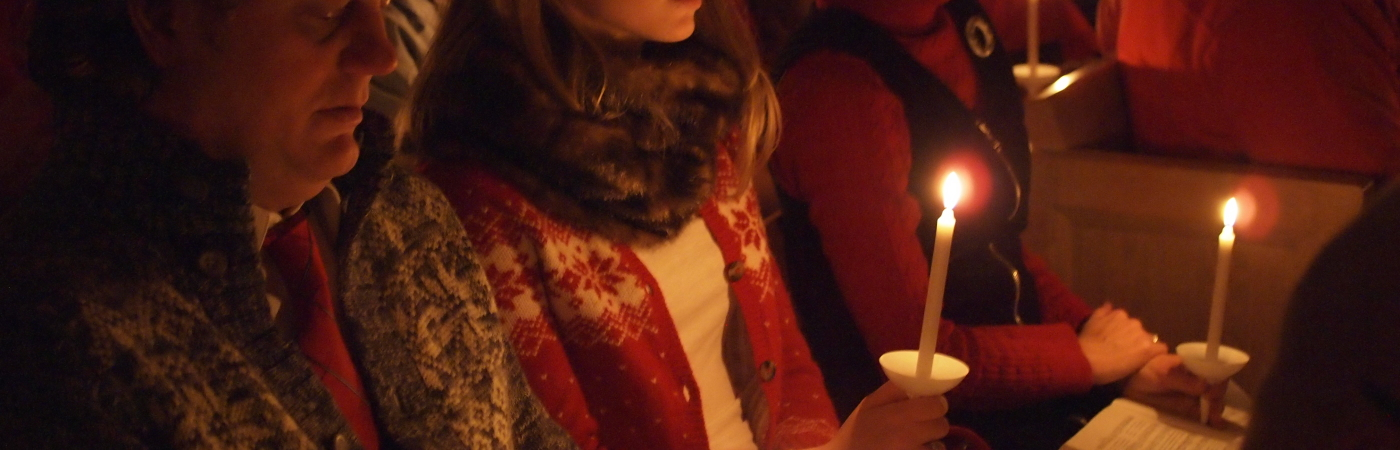 "Family holding candles while singing ""Silent Night"""