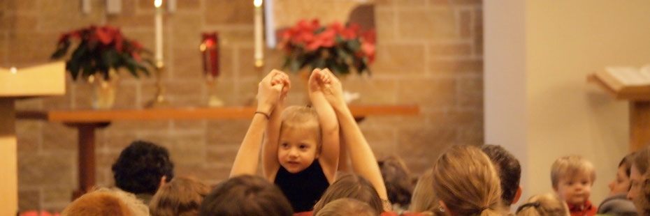 A Young Child lifts her hands up at Christmas Service with others sitting in the Pews