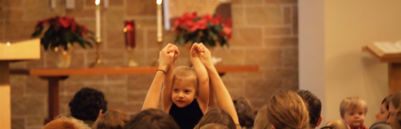 A child with arms upraised during a Christmas service