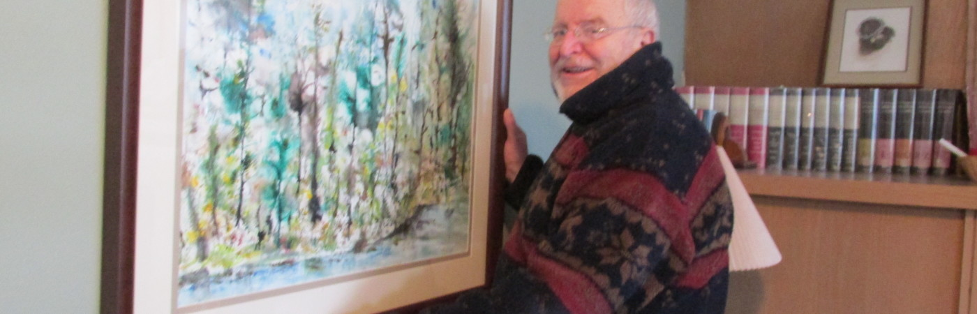 Steve Coll hanging one of his paintings