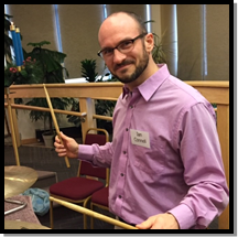 Ian - white man with beard, glasses, wearing lavender shirt with raised drum sticks